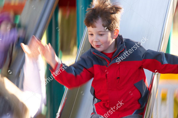 stock-photo-little-boy-sliding-down-a-slide-at-the-park-with-motion-blur-297628157